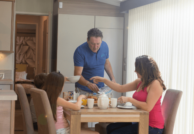Holgates Holiday parks in Lancashire -family enjoying breakfast in a caravan